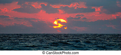 cloudy sunset panorama under sea waves surface