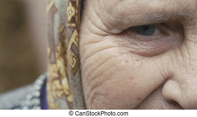 Clous-up Portrait of old tired alone grandmother's eye looking at camera