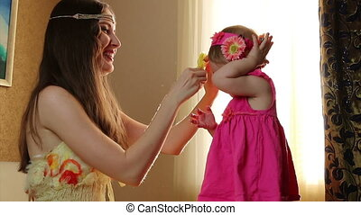 Clouse-up portrait. Mom puts little daughter flowers on hair. small child playing with his mother in the room on a bed