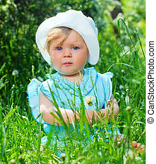 little girl sitting in the grass in the park