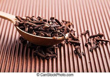 clove in a wooden spoon on a brown background