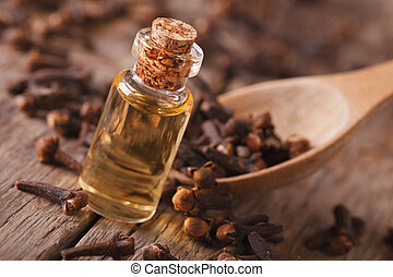 Clove oil in a bottle close-up on the table. horizontal, rustic style