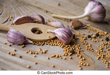 Cloves of garlic, mustard seeds and spoon on wooden board. Rustic style garlic on vintage wooden background. Fresh garlic clove. Garlic bulbs