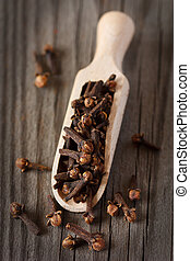 Spicy cloves in a wooden scoop on an old board.