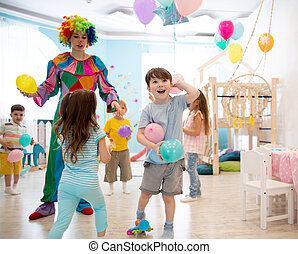 Clown entertains children at birthday party. Kids play with colorful ballons