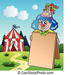 Clown holding board near tent