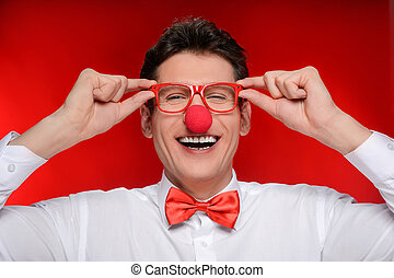 Clown in eyeglasses. Cheerful man with clown nose touching his eyeglasses while standing isolated on red