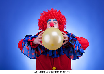 Clown in red costume with balloon in hands