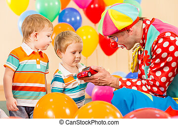 clown making present child boy on birthday party