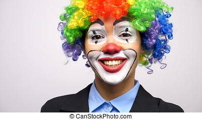 Clown wearing a colorgul wig looking and smiling at the...