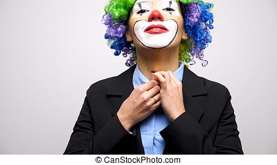 Clown with a wig and business suit closing the button from...