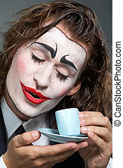 Clown with coffee - Portrait of man with painted face...