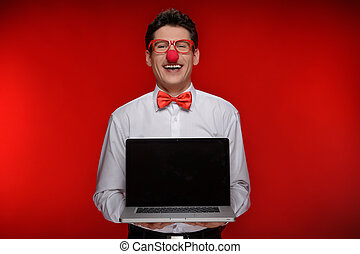 Clown with laptop. Cheerful man with clown holding a laptop while standing isolated on red