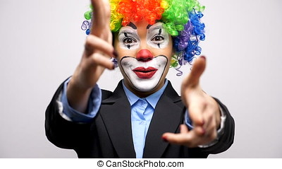 Clown woman in business suit and colorful wig making gun...