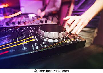 Club DJ playing mixing music on vinyl turntable