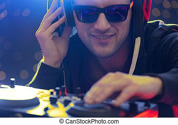 Club dj playing music during night party