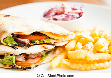 Club sandwich in pita with fried potato and salad