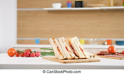 Club sandwich lying on a plate in the kitchen