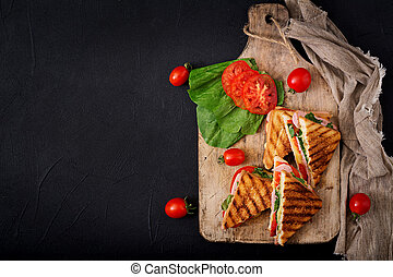 Club sandwich panini with ham, tomato, cheese and basil....