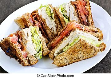 Club sandwich - Toasted club sandwich sliced on a plate