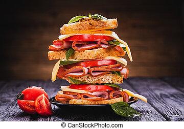 Club sandwich with cheese, basil, tomato, ham