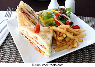 Club sandwich with french fries and salad