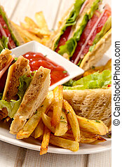 Club sandwiches and french fries in the plate on wooden background, selective focus