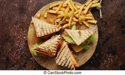 Club sandwiches served on a wooden board. With hot French fries. Filled with chicken, cheese, lettuce, tomato and onion. Fast food concept. Flat lay.