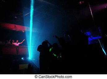Clubbers at night - Club shadow play. Motion blurred DJ...