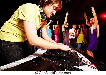 Clubbing - Smart deejay working at disco with dancing teens...