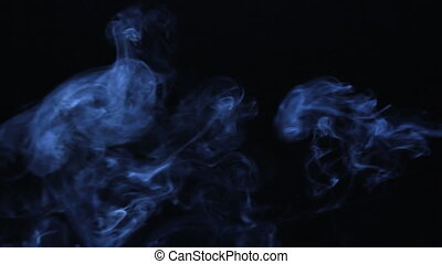 Clubs of blue smoke on a black background. Beautiful