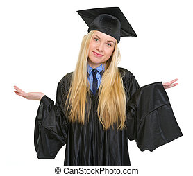 Clueless young woman in graduation gown shrugging shoulders