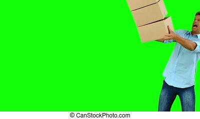 Clumsy man dropping boxes over on green screen in slow...