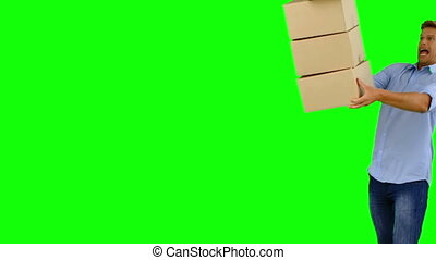 Clumsy man dropping boxes down on green screen in slow...