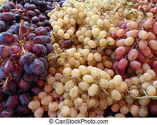 Cluster of 3 colors of grapes on open air for sale at an open market