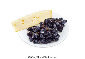 Clusters of blue grapes and piece of Swiss-type cheese
