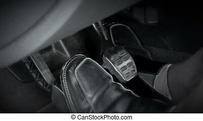 This is a shot of a sports car's pedals. The driver changes feet quickly as he's shifting through gears.