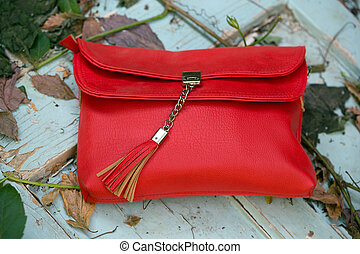 clutch - small red handbag on a on a wooden background with...