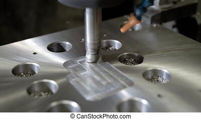 CNC machine is whittling hole in a metal detail in a plant,...