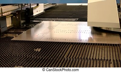 Cnc punching machine in action. Metal sheet with holes....