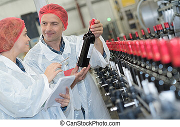 co-worker showing newly produced bottle of wine on winery manufactory