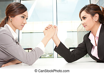 Two young asian co-workers aggressively arm wrestling for dominance.