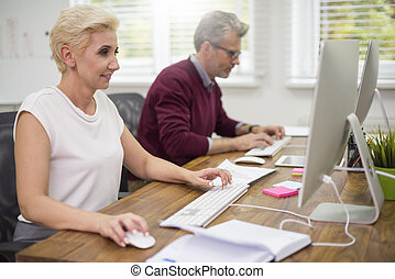 Co workers busy in front of computers