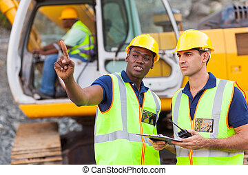 co-workers talking at construction site with bulldozer...