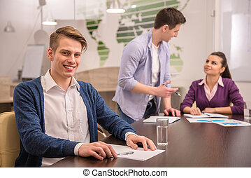 Co-working - Smiling young business man is looking at the...