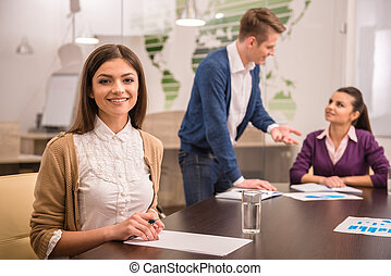 Co-working - Smiling young business woman is looking at the...