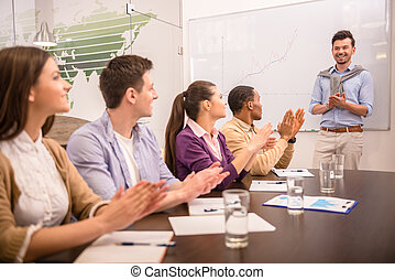 Co-working - Cheerful business people applauding in a...