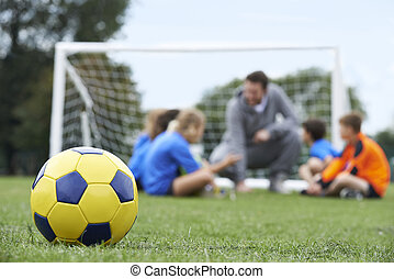 Coach And Team Discussing Soccer Tactics With Ball In ...