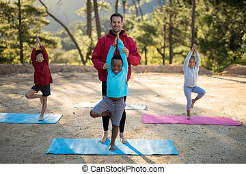 Coach assisting kids in practicing yoga on a sunny day