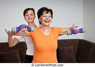 Coach assisting senior woman exercising with barbells -...